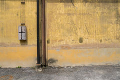 Texture of old yellow vintage wall of industrial factory with rusted iron pole Royalty Free Stock Image