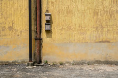 Texture of old yellow vintage wall of industrial factory with rusted iron pole and electric cable Stock Image