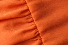 Texture of orange fabric with folds as background royalty free stock photo