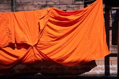 Texture of orange robe of a buddhist monk or novice hanged on wire. Texture of orange robe of a buddhist monk or novice stock images