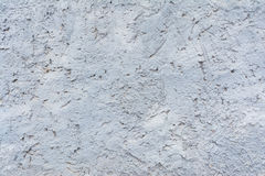 Texture of painted plaster of rough embossed wall of outer basement of building, blue background Stock Photos