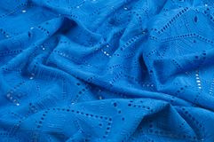 Texture pattern. Cloth blue dense with perforated holes. For the. Avant-garde or not very serious take in your design. Covered in different areas round holes royalty free stock image