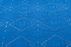 Texture pattern. Cloth blue dense with perforated holes. For the. Avant-garde or not very serious take in your design. Covered in different areas round holes stock photo
