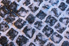 The texture of paving stone masonry sprinkled with snow, close up. Royalty Free Stock Photos