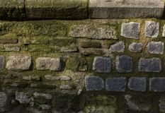 Texture of pebble paving. Ancient brick wall with moss royalty free stock image