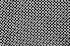 Texture of perforated metal sheet stamped or punched to create a XO pattern royalty free stock photography