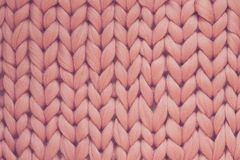 Texture of pink knit blanket. Large knitting. Plaid merino wool. Top view Royalty Free Stock Photo