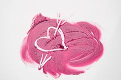 The texture of pink lipstick drawn heart pierced by an arrow, love, cheating, make-up.  Stock Photos