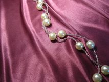 Texture of pink silk with beads from pearls. On pink silk with drapery pearl beads Royalty Free Stock Photo