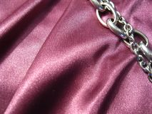 Texture of pink silk with a metal chain element. On pink silk with drape, an element of a metal chain Royalty Free Stock Photo