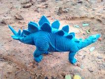 Blue dinosaur. Animal toy on ground nature Stock Image