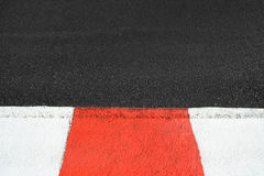Texture of race asphalt and curb on Grand Prix circuit. Texture of motor race asphalt and re white curb. Close up on Monaco Montecarlo Grand Prix street circuit Stock Image