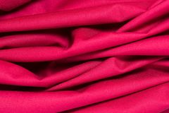 Texture of red cotton fabric with arbitrary bends and wave, abstract background Royalty Free Stock Photo