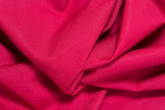 Texture of red cotton fabric with arbitrary bends and wave, abstract background Stock Photo
