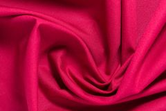 Texture of red cotton fabric with arbitrary bends and wave, abstract background Stock Image