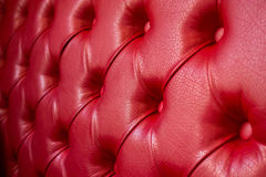 Texture of red leather sofa. Focus on the center. Royalty Free Stock Images