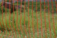 Texture of red plastic mesh fence on a background. Of green grass royalty free stock images