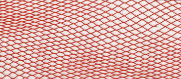 Texture - red plastic mesh for packaging, transportation and sale of vegetables. Royalty Free Stock Photo