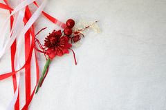 Texture red shiny artificial decorative flower decorated with balls with red and white beautiful festive ribbons made of artificia. L fabric on a light gray Royalty Free Stock Images