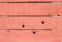 Texture: Red Wood Wall. A rather crude wall of wooden planks, with fading red paint. Useful for textures and backgrounds Stock Image