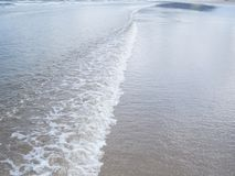 Texture of ripples with foam at the seaside. Ripple texture, with foam at the seaside, in shallow sea Stock Images