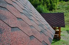 The texture of the roof with bituminous coating. Rough bituminous mosaic of red and brown flowers. Waterproof roofin Stock Images