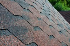 The texture of the roof with bituminous coating. Rough bituminous mosaic of red and brown flowers. Waterproof roofin Royalty Free Stock Photos