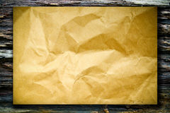 Texture of rough crumpled paper on wood board Stock Photos