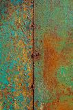 Texture of rusty metal, painted green which becames orange from rust. Vertical texture of cracked paint on rusty welded steel. Texture of old rusty metal royalty free stock images