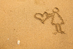 In texture of sand: girl holding a big heart. Love. Stock Photos