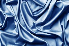 The texture of the satin fabric of blue color for the background stock images