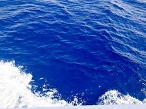 He texture of a seething blue sea water with waves, bubbles, foam, traces after a fast floating cart, a boat. The background stock image