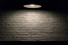 Texture Series - White Brick Wall with Overhead Lamp. Image showing a brick wall painted white that is illuminated from above with a nice overhead lamp royalty free stock photography