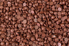 Texture of small chunks of sweetened chocolate chips background. Closeup texture of small chunks of sweetened chocolate chips background Royalty Free Stock Photo
