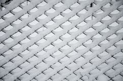 Texture of snow on the fencing net. Metal wire mesh covered with snow in winter. Beautiful winter. White snow on wire metal mesh fence. Blurred snowy nature on stock photography