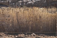 Texture of soil with traces of a bucket of excavator. Wall ground of section quarry pit for foundation building construction stock photography