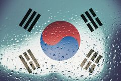 Texture of the South Korea flag. Texture of the South Korea flag on the glass with drops of rain at dawn stock images