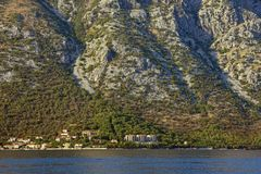 The texture of steep mountain slope, illuminated by the sun, with a small seaside village at the foot. Montenegro, Bay of Kotor. The texture of the steep stock images