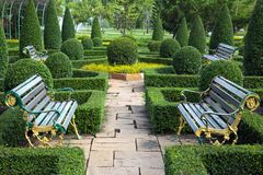 Garden design with stone mix. Texture of stone pathway in garden. Two benches in the garden royalty free stock photo
