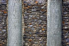 The texture of the stone from the wall of colored cobblestones and brick columns Stock Images