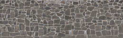 Texture of a stone wall. Old castle stone wall texture background. Stone wall as a background or texture. An example of masonry as a cladding of external walls royalty free stock photo