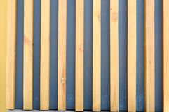 Texture of striped yellow and brown vertical wooden poles and boards with gray gaps, slits. The background royalty free stock photo