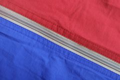Texture of the surface of two colored fabric with a zippered diagonal lock. Texture of the surface of blue and red fabrics with a zippered diagonal lock Stock Photography