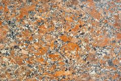 Texture - the surface of a granite slab with orange impregnations. Background, texture - variegated surface of polished granite slab with orange splashes Royalty Free Stock Photography