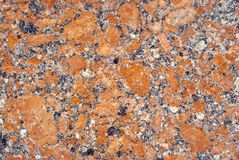 Texture - surface of a granite slab with orange splashes. Background, texture - variegated surface of polished granite slab with orange impregnations Stock Image