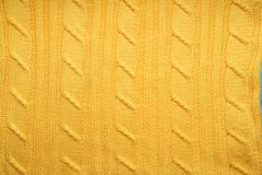 The texture, surface of a knitted woolen fabric. Background, backdrop to create a winter layouts, Christmas cards, banners. Knit yellow sweater Royalty Free Stock Photography