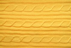 The texture, surface of a knitted woolen fabric. Background, backdrop to create a winter layouts, Christmas cards, banners. Knit yellow sweater Stock Photos