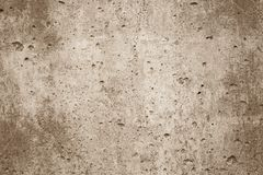 Sepia background wall. The texture of the surface of the old wall is light brown in color with many small holes, dots and scuffs. The central part is lighter stock image