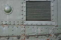 Texture of tank side wall, made of metal and reinforced with a multitude of bolts and rivets. Image of covering of a combat vehicle from the Second World War royalty free stock photography