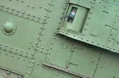 Texture of tank side wall, made of metal and reinforced with a multitude of bolts and rivets. Image of covering of a combat vehicle from the Second World War royalty free stock images